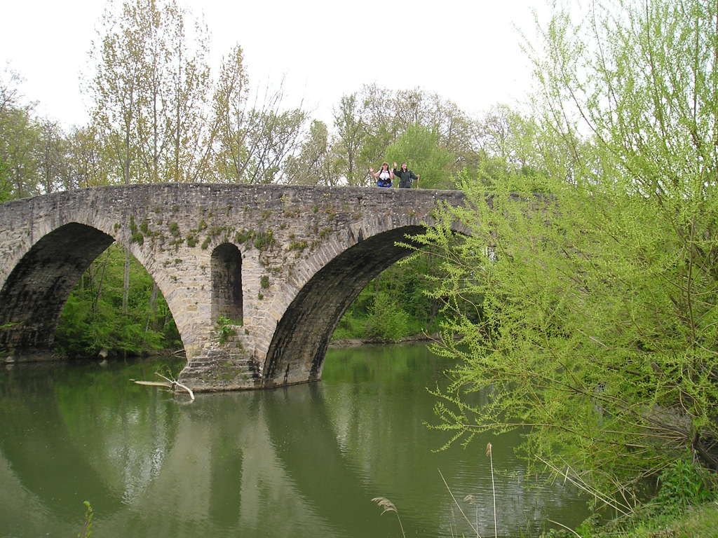 Two friendly pilgrims walking across a bridge in lush green Camino surroundings